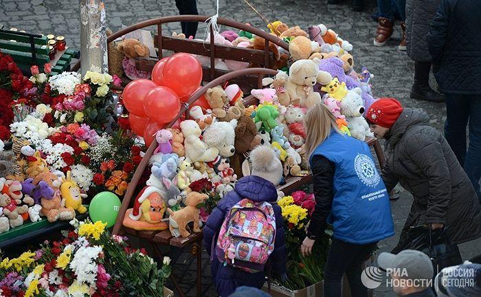 Жители несут цветы и мягкие игрушки к зданию торгового центра «Зимняя вишня» в Кемерово, где произошел пожар. Фото: РИА Новости / Александр Кряжев